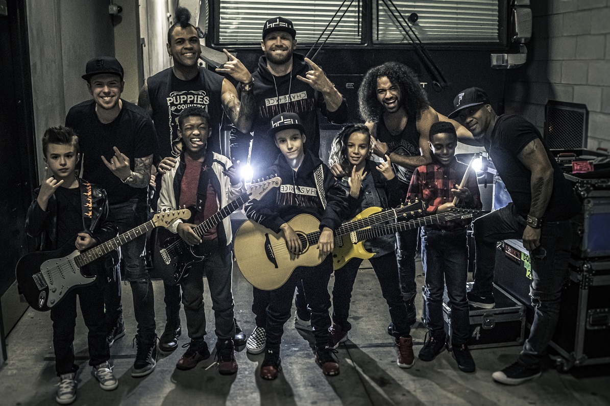 """Chase Rice & bandmates (back row L to R: Chris Loocke/lead guitar, Marcelo Bakos/bass, Rice, John Souki/rhythm guitar, Jeremy Roberson/drums) pose backstage with the young stars of the """"Lonely If You Are"""" official music video   Photo Credit: Cody Cannon"""